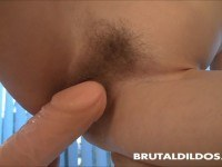 Fucks her hairy pussy with a big dildo